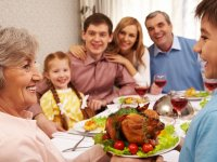 pressmaster: Portrait of happy grandmother holding tray with roasted turkey and looking at her grandson